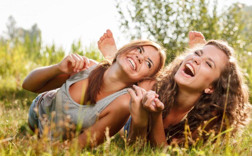 2 veninder der ligger i græsset og griner